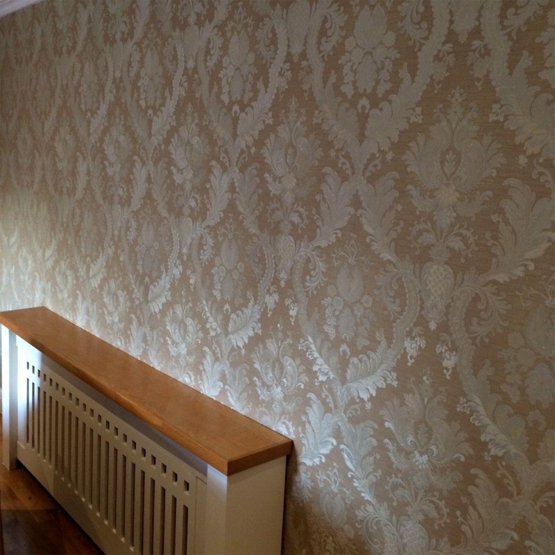 Wallpapering around a radiator in a Dublin home by Abhaile Decorators, Ireland